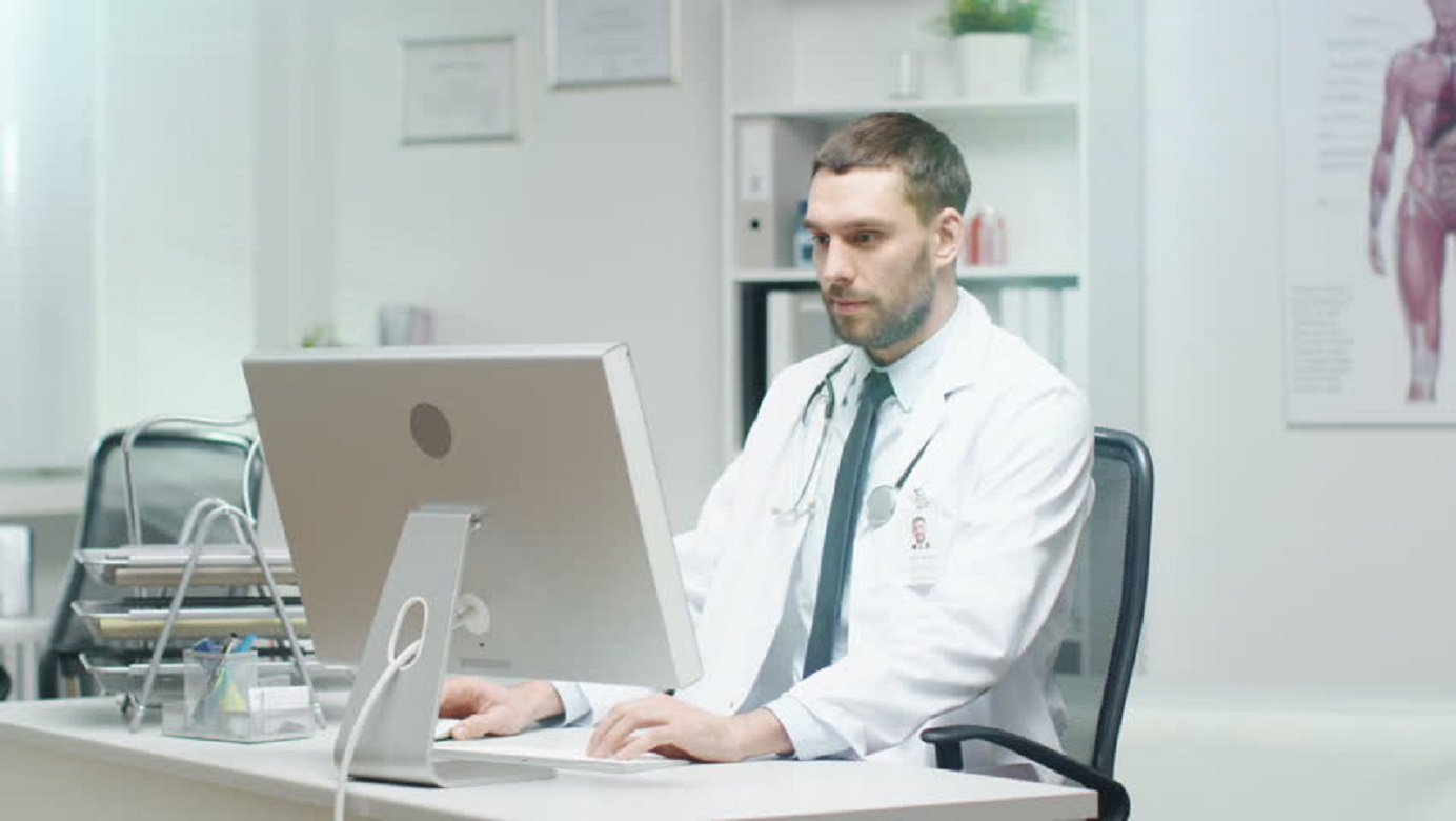 A physician watching Business Courses to learn more about the business side of being a doctor by watching videos.