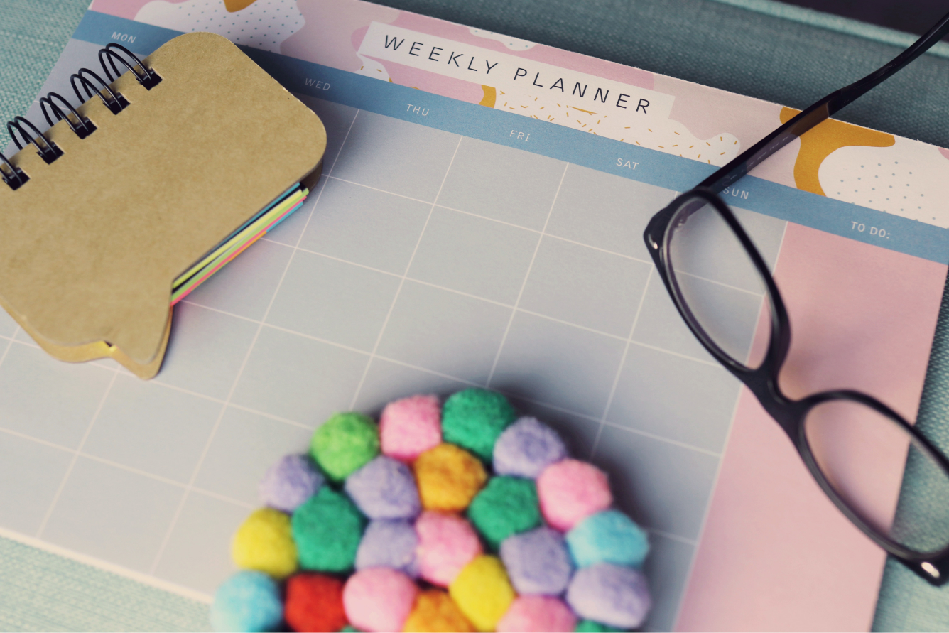 A weekly planner sits on a desk with a notebook and a pair of reading glasses