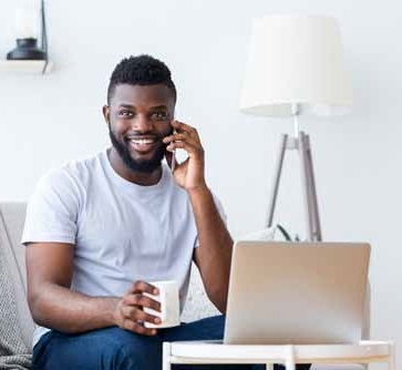 man with mobile phone, cup of coffee and laptop