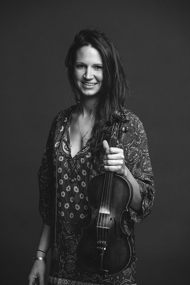 A black and white picture of Aurora holding a fiddle and smiling