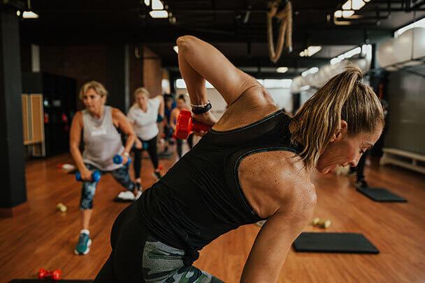 Entrenadora de deporte realiza ejercicios funcionales con una mancuerna frente a un grupo de mujeres en un centro de entrenamiento.