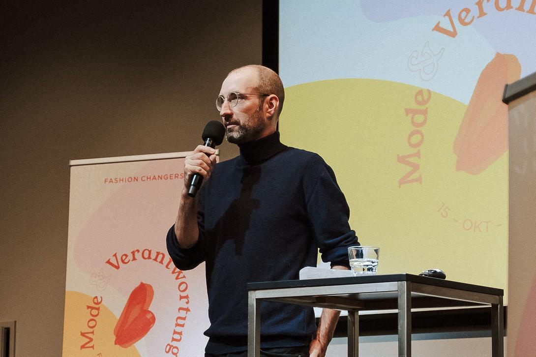 Mann mit Rollkragen Pullover und Brille steht auf der Fashion Changers Konferenzbühne und hält einen Vortrag