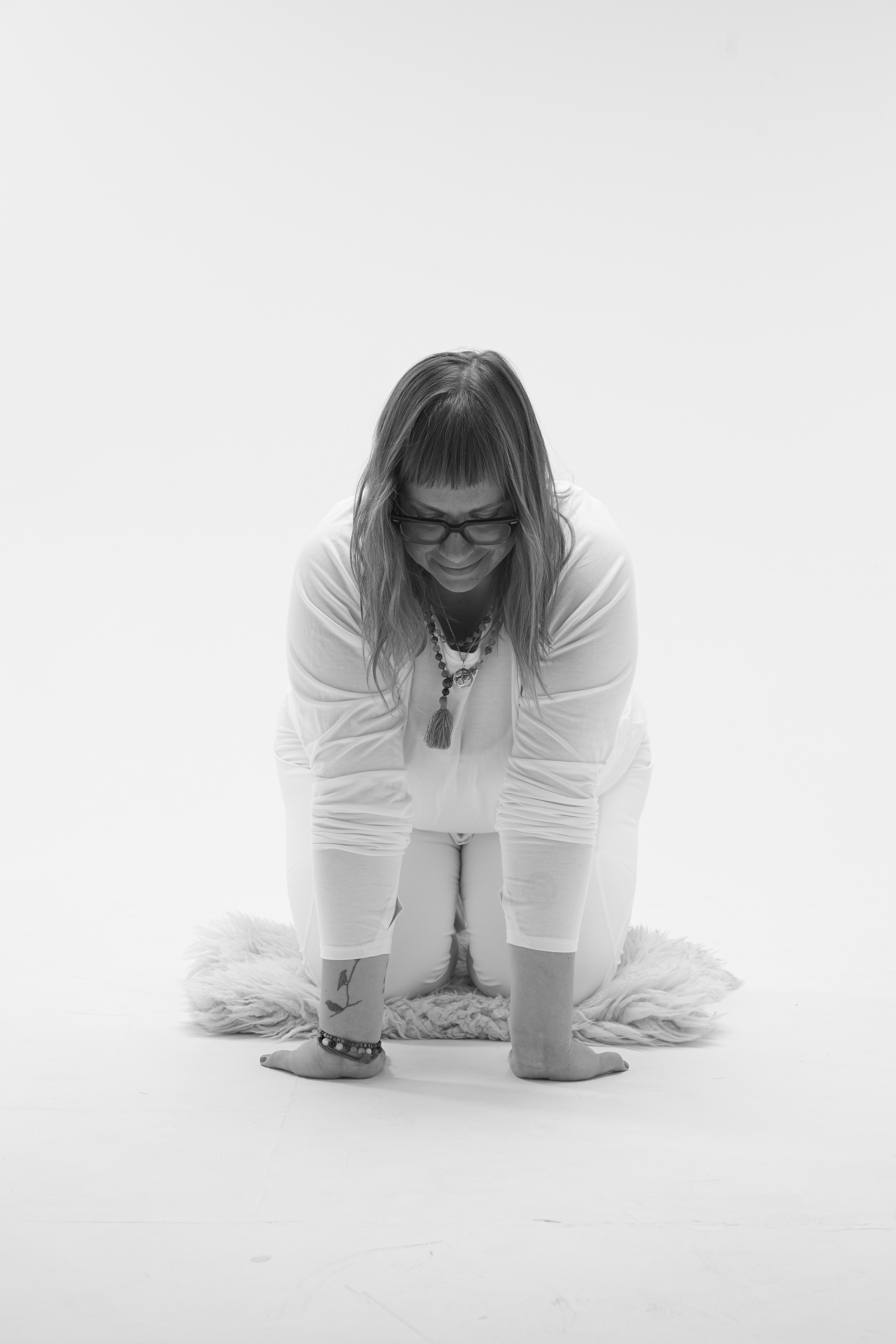 black and white image of yin yoga teacher Amanda Flott-Kinsey demonstrating big cat pose
