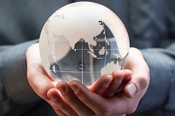 Man's hands cupped together cradling a small globe