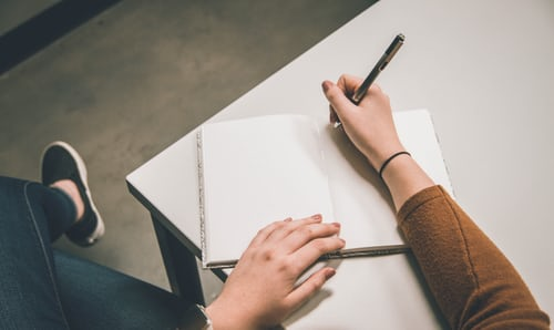 An open notebook on a desk with a hand holding a pen over it
