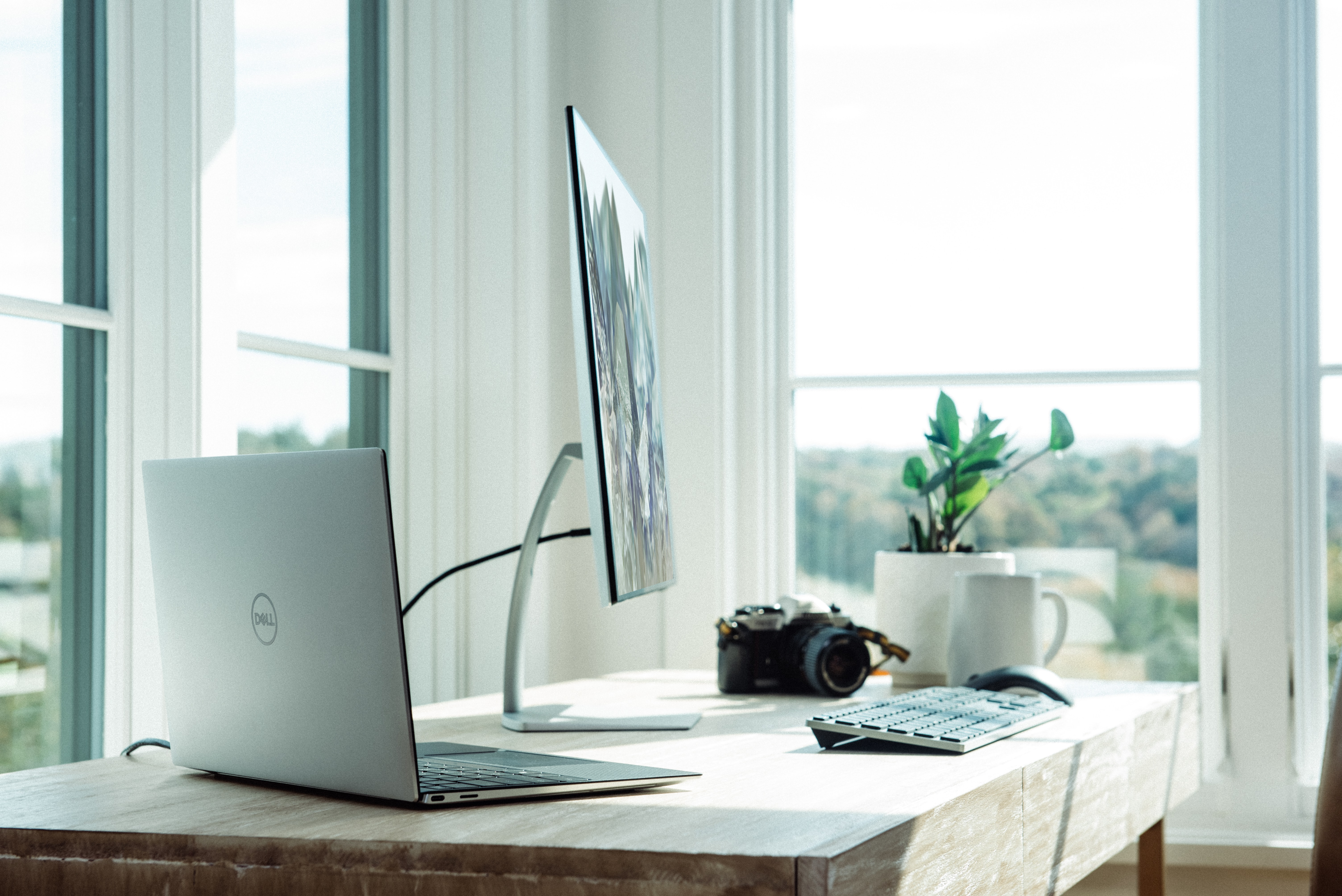 Office desk with computer, monitor, camera and 3 windows in the background