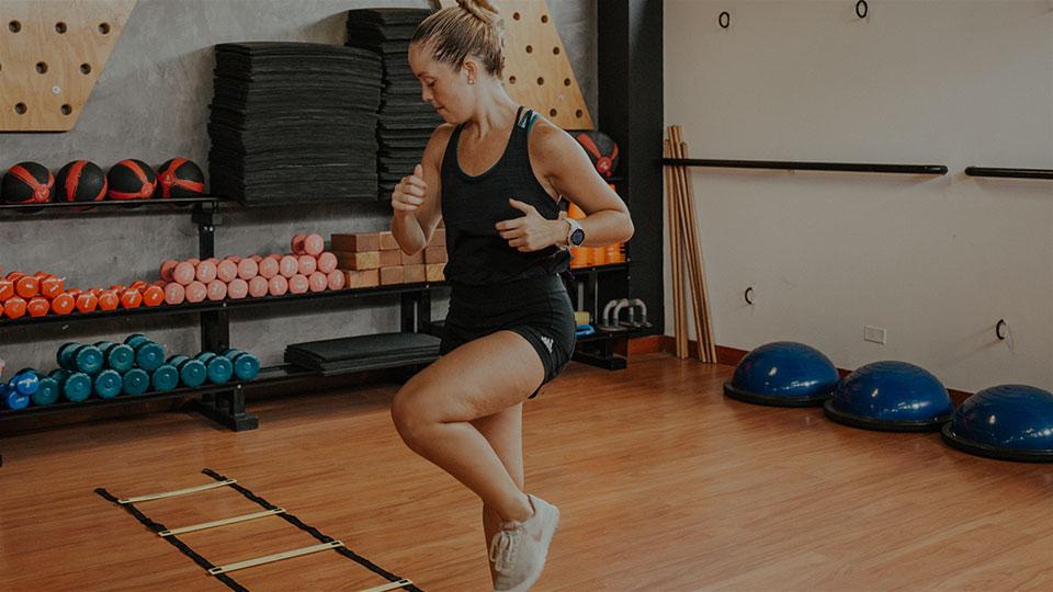 Mujer entrena levantando la rodilla en una escalera de piso