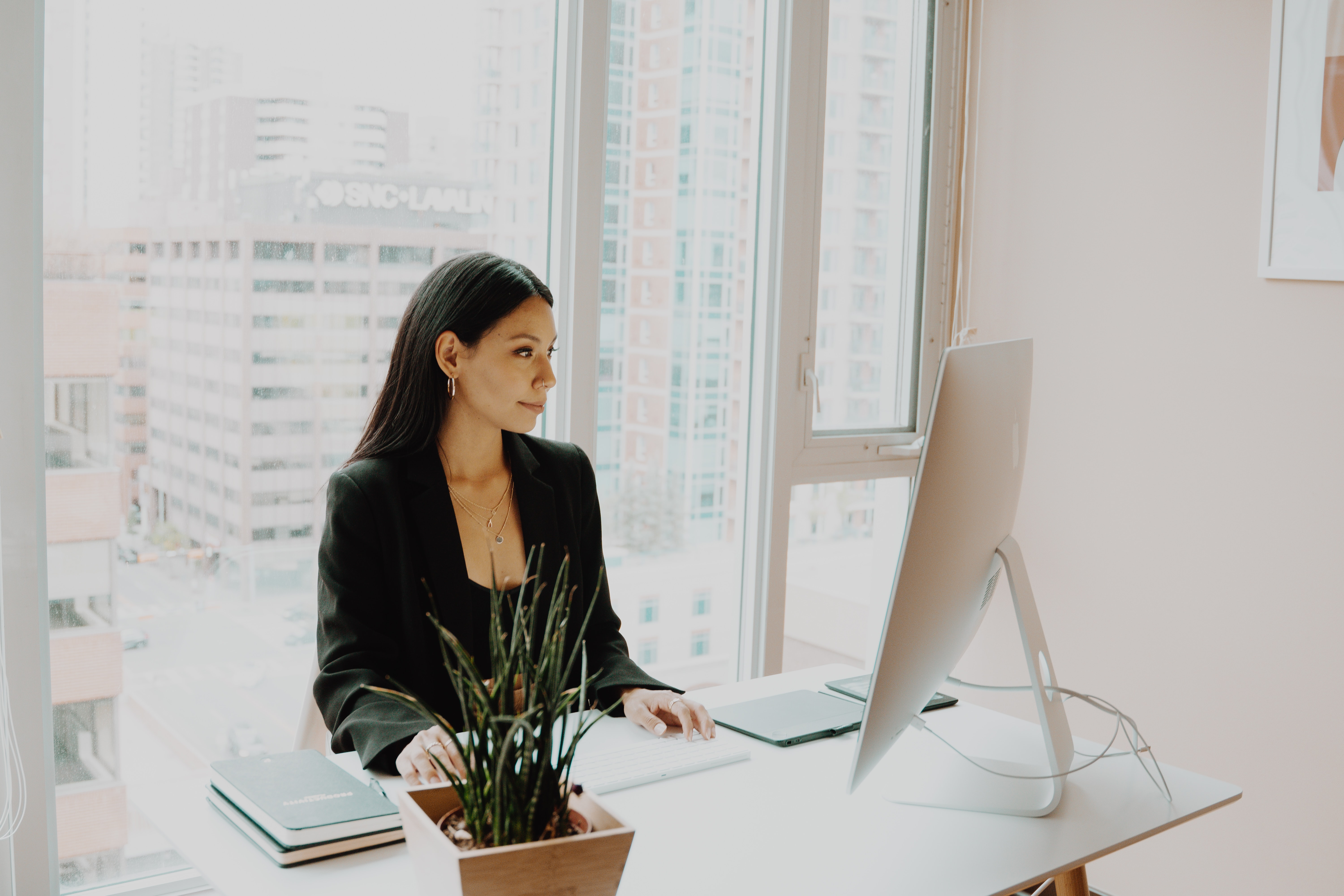 woman sits at a desk with computer with window and city scape through windows behind her