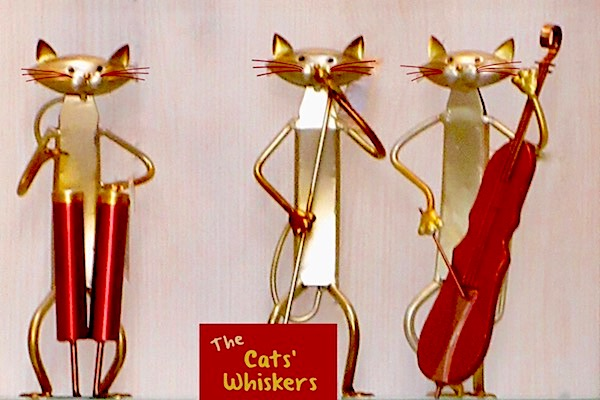 A trio of three bronze cat statues playing musical instruments and singing