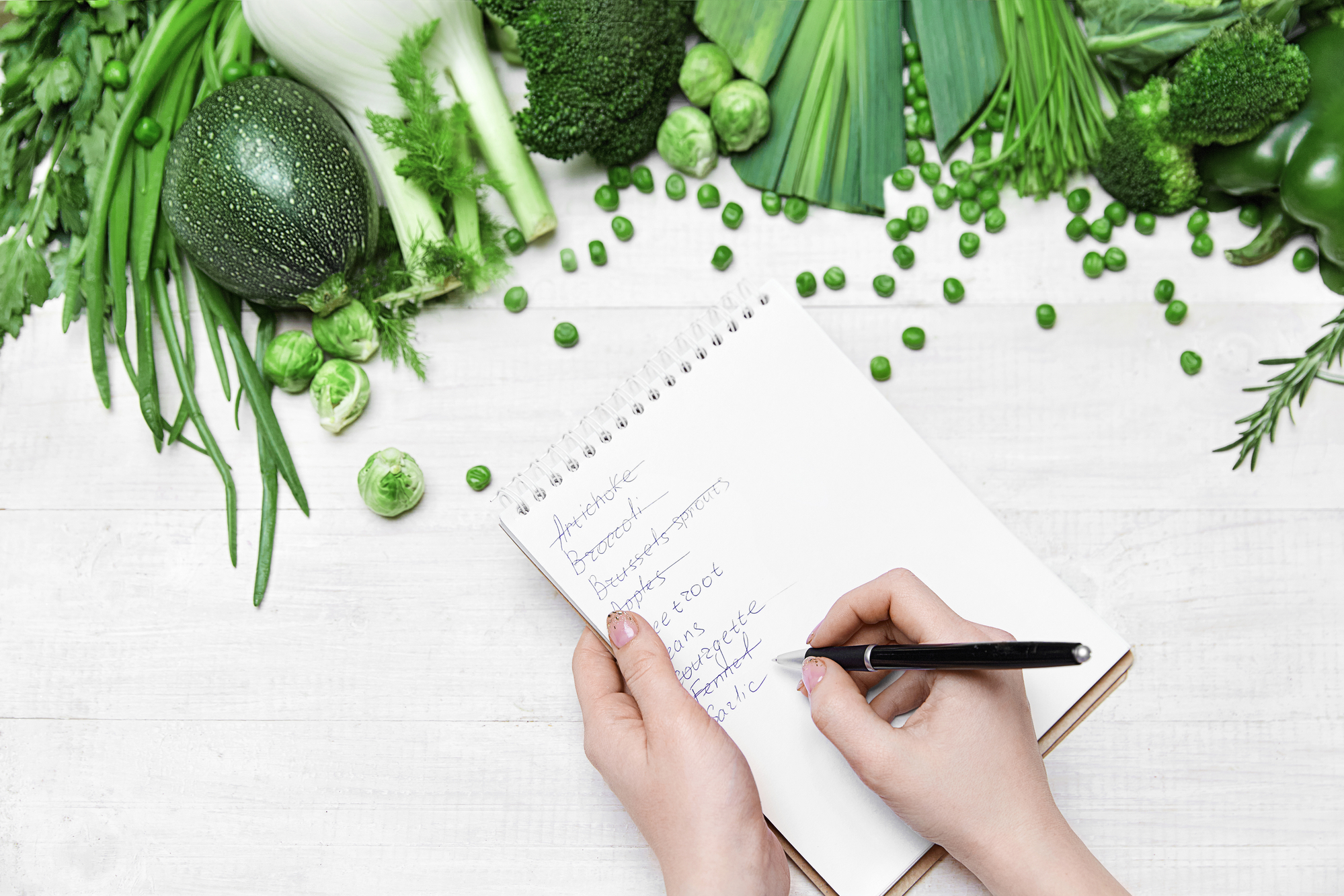 womans hands writing a shopping list against background of green vegetables