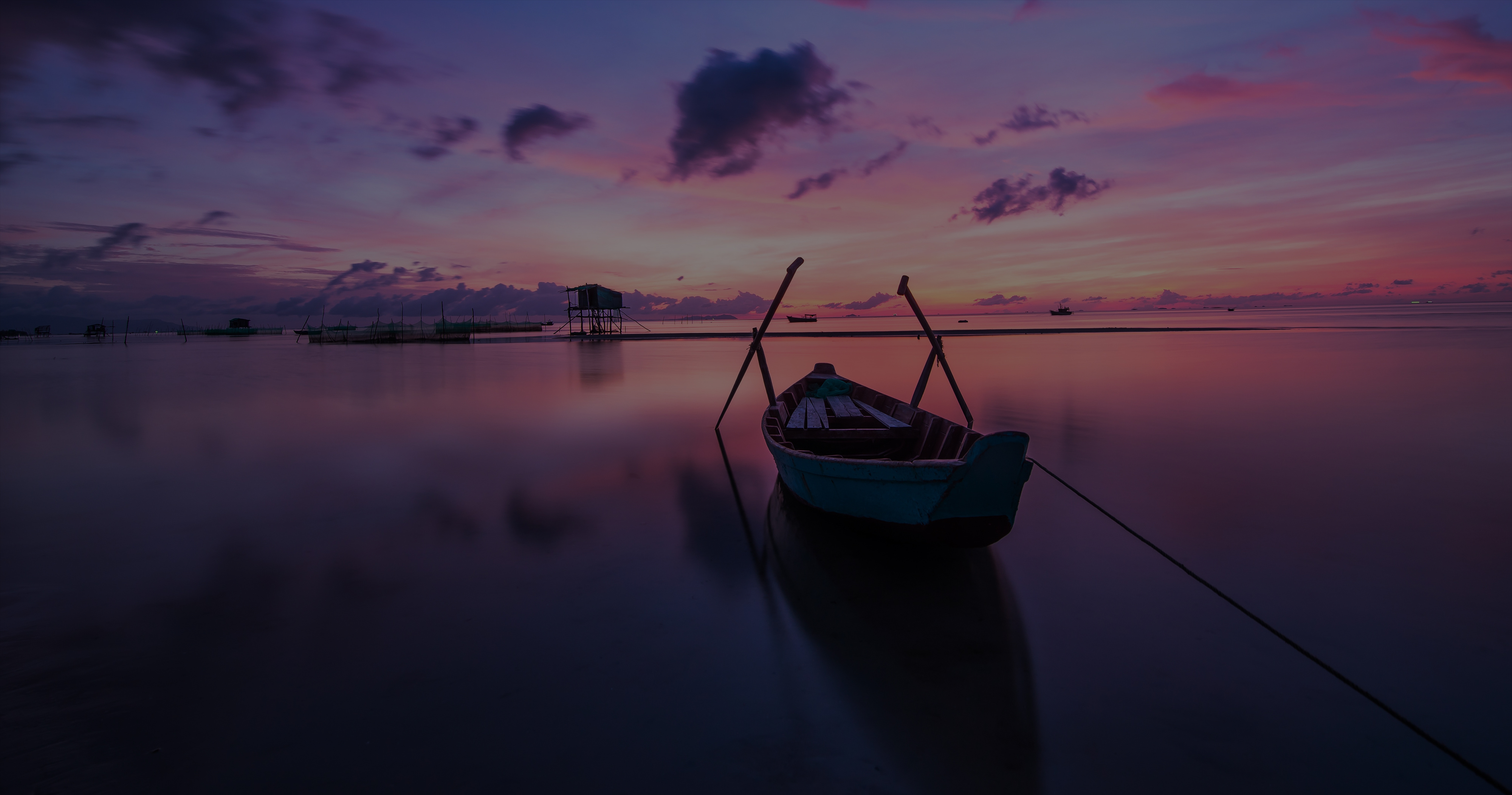 photo of lone boat on still water at sunset