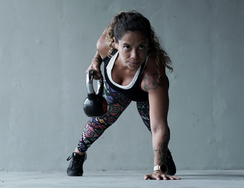 Mujer en ropa deportiva se apoya en el piso mientras realiza ejercicios funcionales con un kettlebell en la mano derecha.