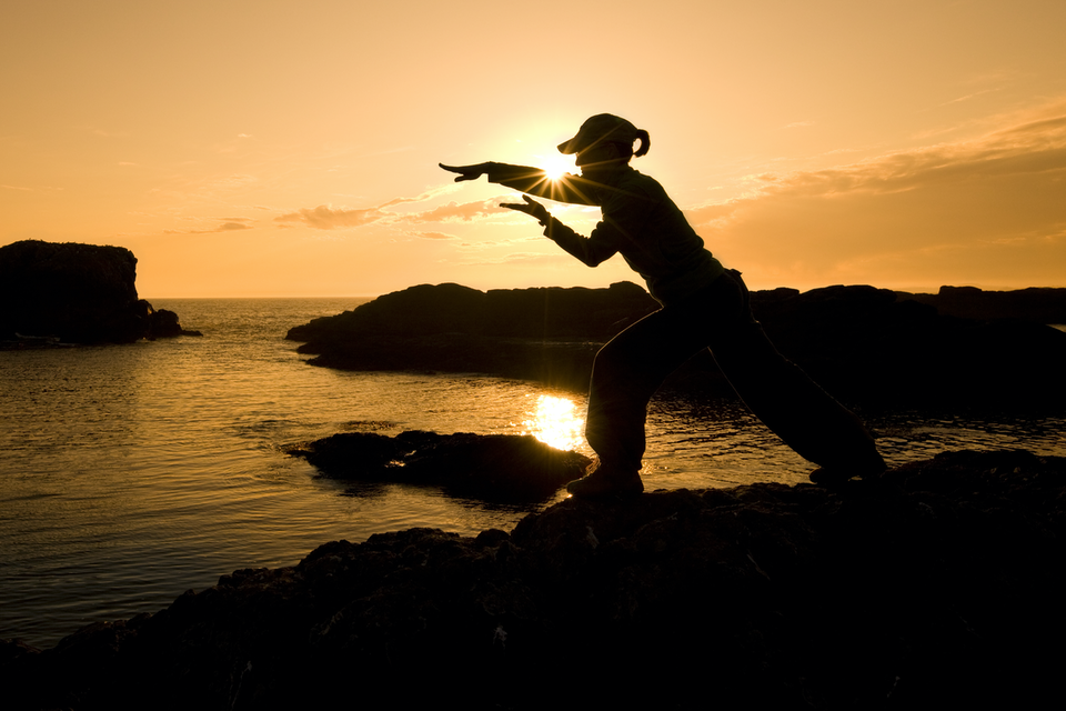Woman doing qigong on rocks