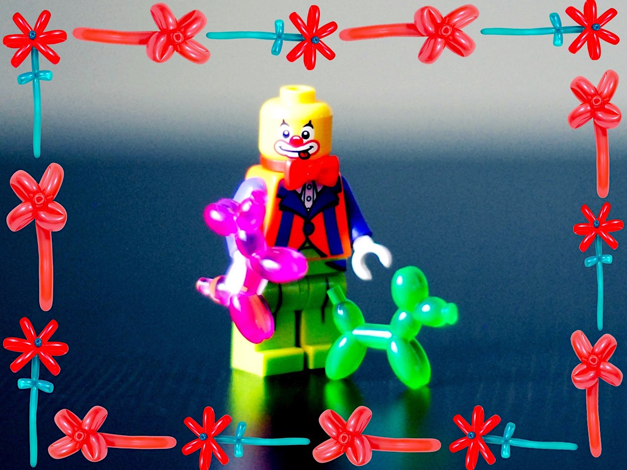 Lego man holding two balloon dogs surrounded by a frame of balloon flowers