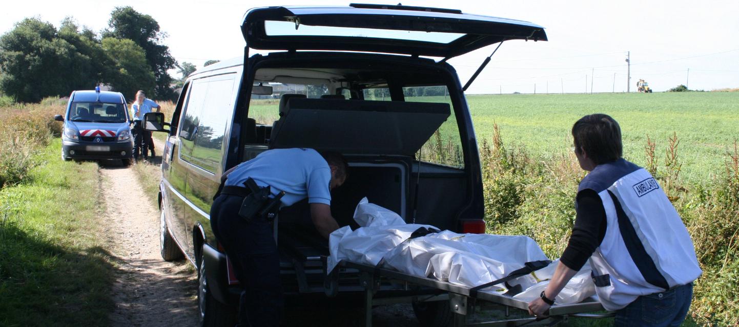 gendarme charge un corps dans un véhicule