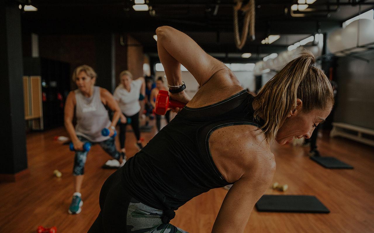 Mujer levanta una mancuerna y guía una clase de entrenamiento funcional para mujeres