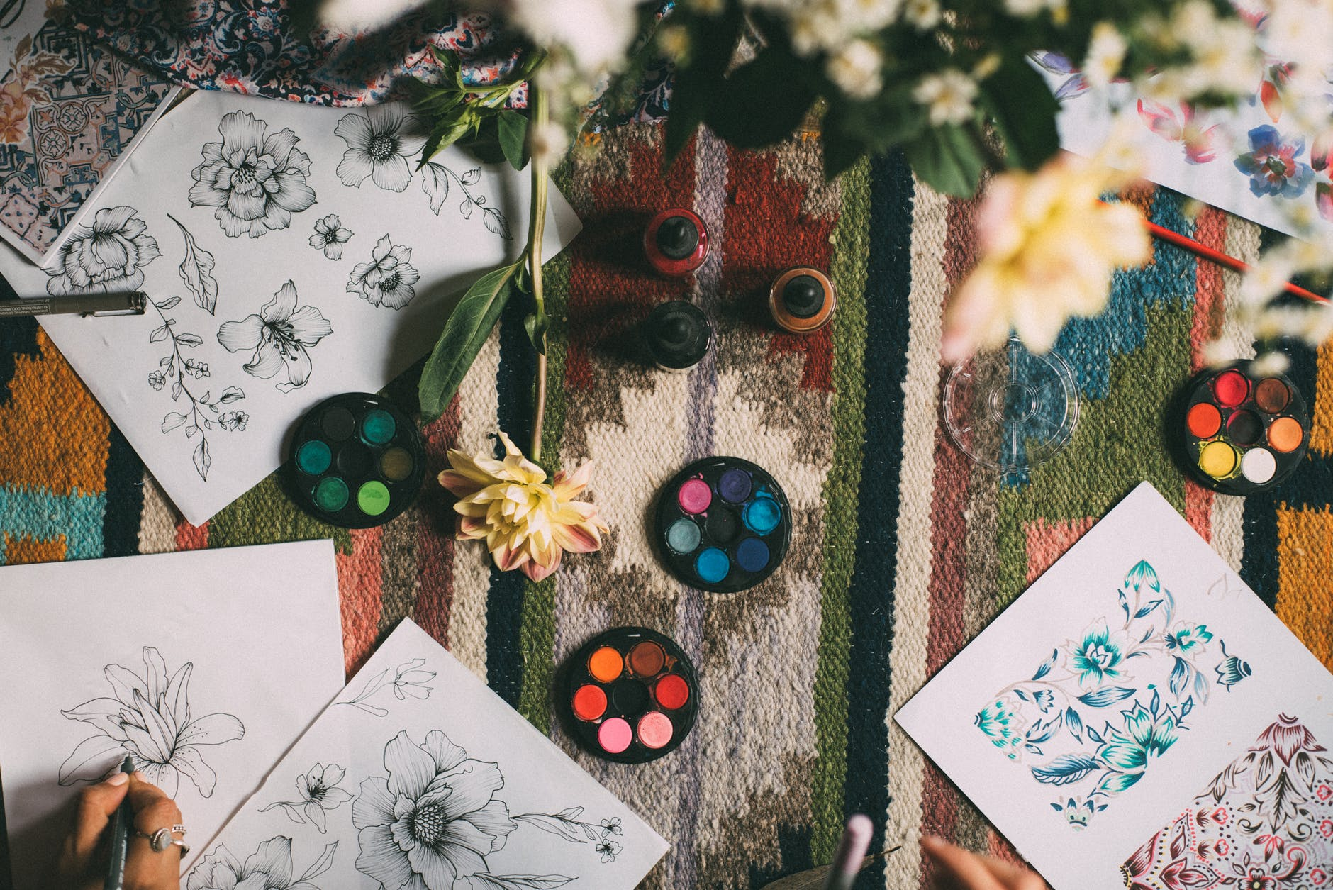 several drawings of flowers and paints layed out on a colourful table