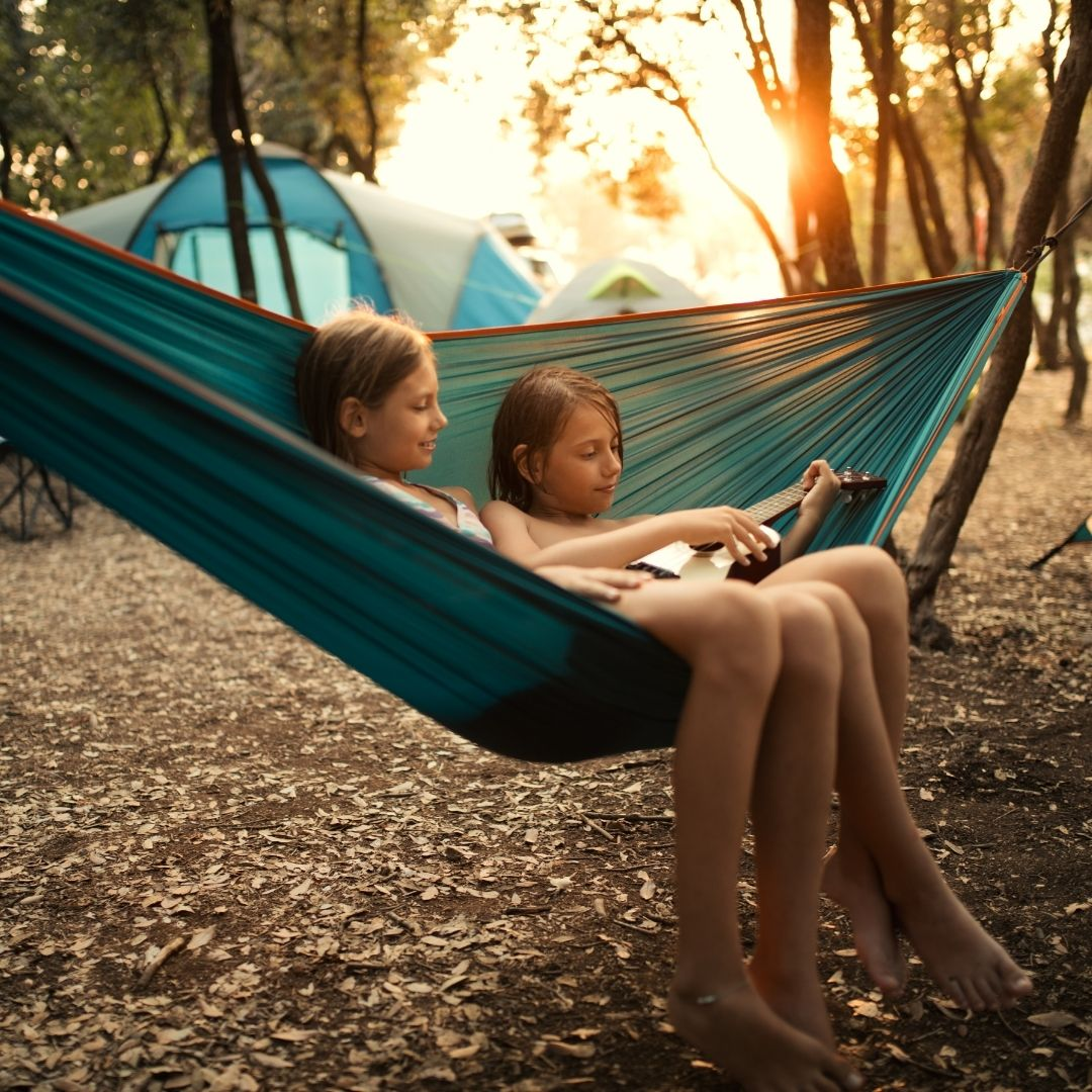 two girls sit in hammock and play ukulele