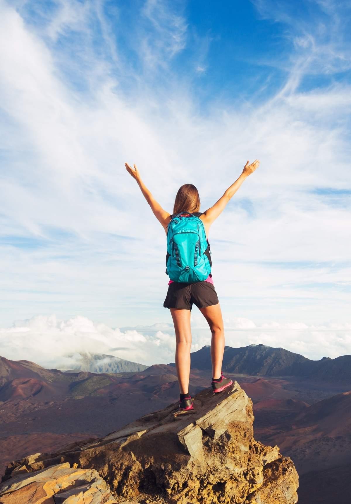 woman hiker celebrating on a mountain