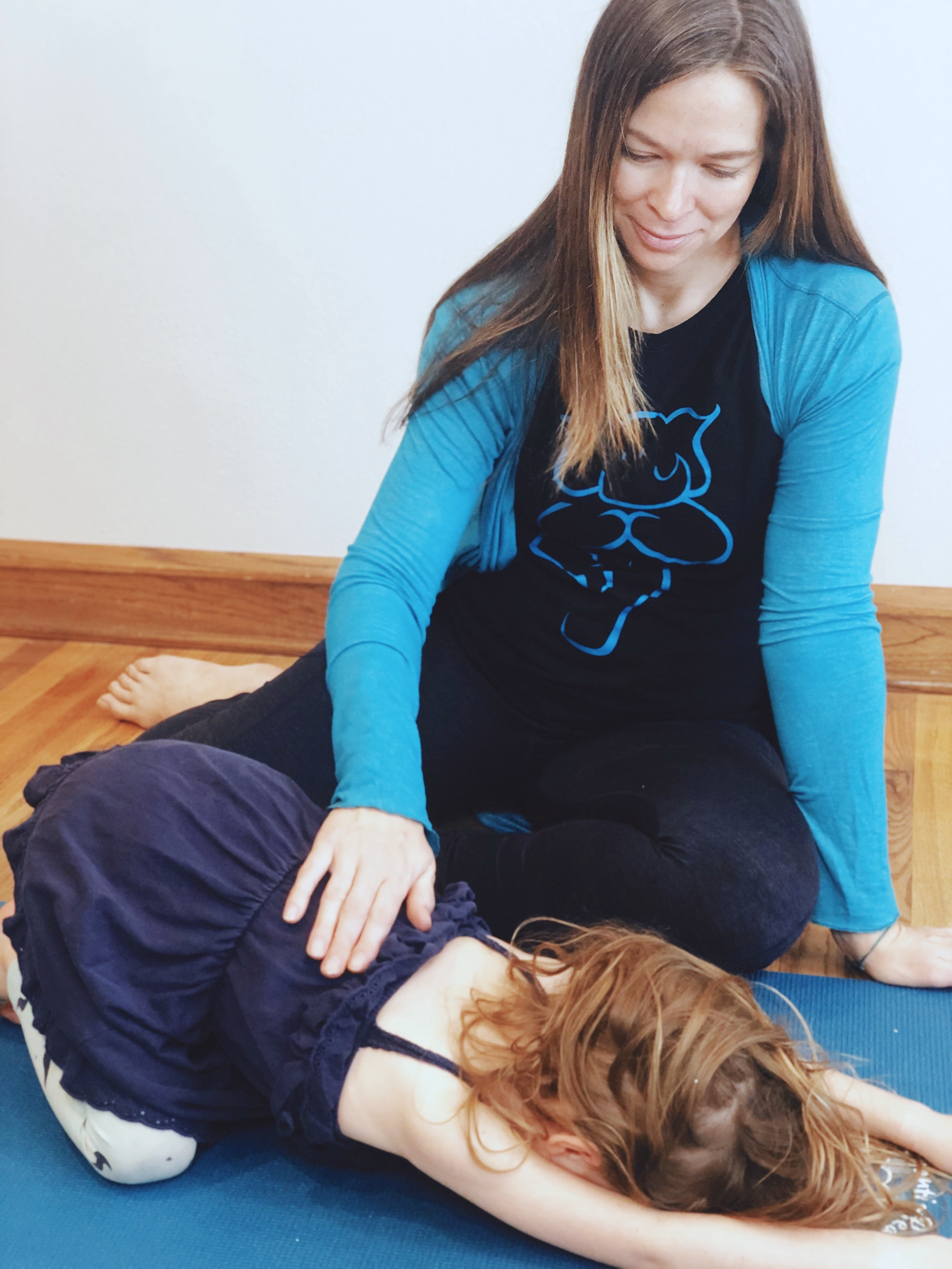 Yoginos instructor guiding student in Balasana or Child