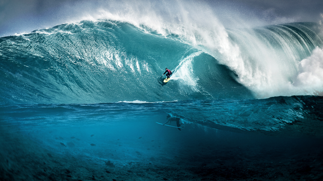 Male surfing below male diving