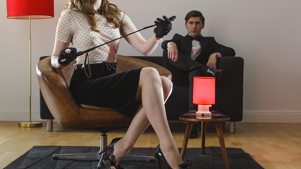 well dressed woman with riding crop and man in tuxedo sitting on couch