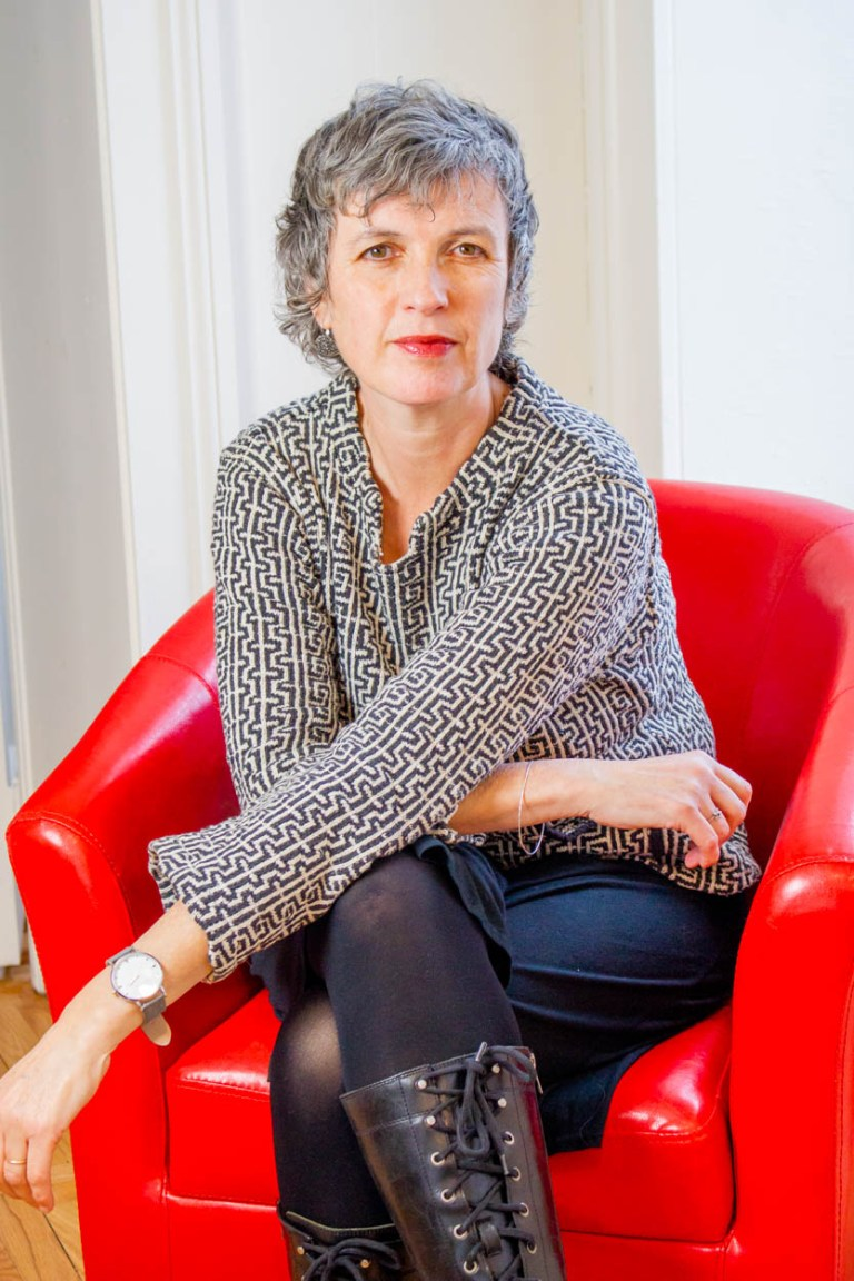 Tosca sitting in red chair against background of white office walls
