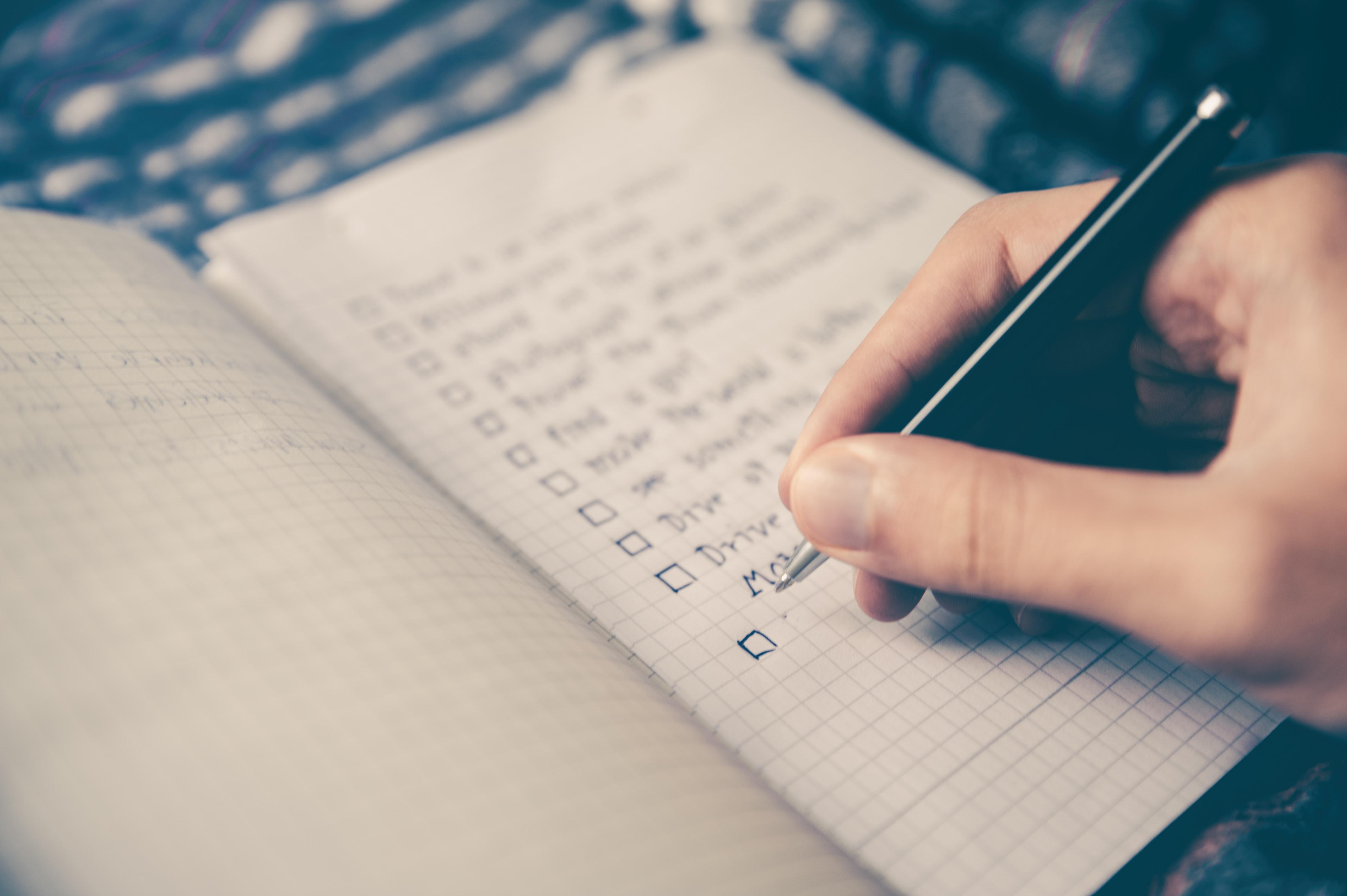Mano escribe una lista de pendientes en un work
