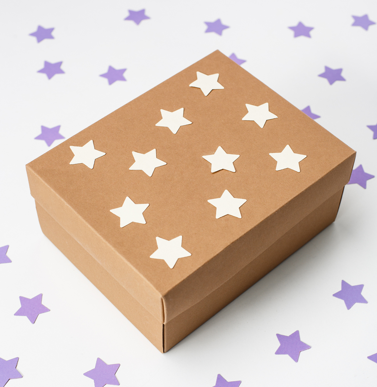 A brown box covered in white stars, sitting on a white table covered in purple stars