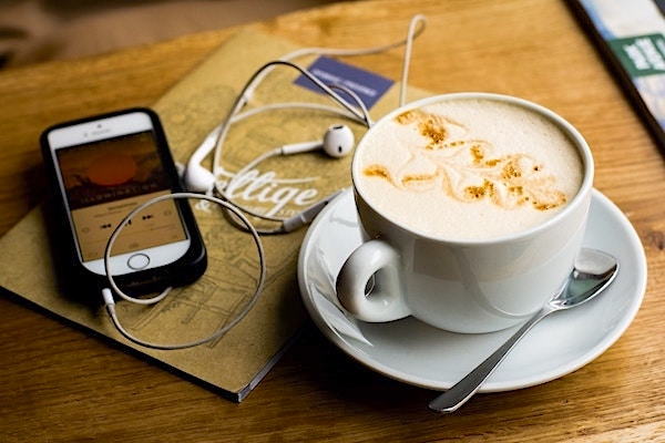 Cup of coffee with a smartphone and headphones next to it
