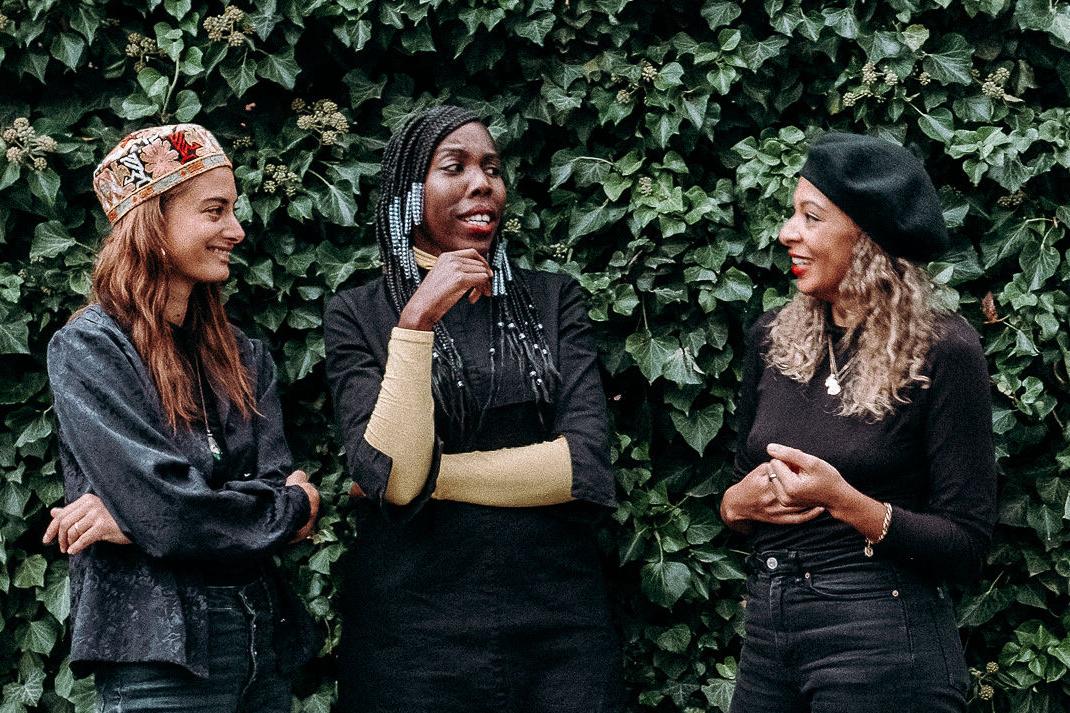 Samira Mahboub, Beatrace Angut Oola und Kemi Fatoba lachen und stehen vor einer grünen Hecke