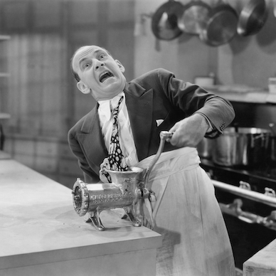 comedy image of man with tie trapped in meat grinder