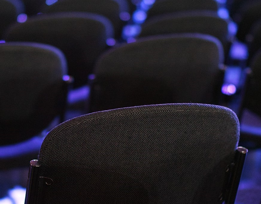 back of conference chairs in neat rows with blue light shining on them